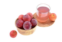 Red plum. Sweet red plum in a wooden bowl and juice isolated on white background Royalty Free Stock Image