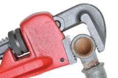 Red plumbers pipe wrench and plumbing component Stock Images