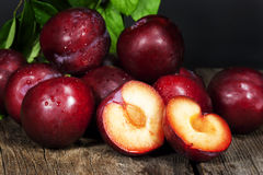 Red Plums. A group of ripe red plums on wood surface, one plum cut in half exposing seed within fruit. Plums belong to the Prunus genus of plants and are royalty free stock photo