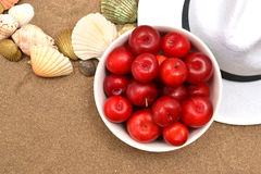 Red plums and shells on sand Royalty Free Stock Photo