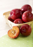 Red plums in small basket 2 Royalty Free Stock Photography