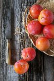 Red plums in wicker basket. On old wooden background Stock Photos