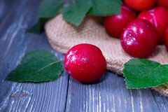 Red plums on wooden table Royalty Free Stock Images