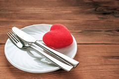 Red Plush Heart with Fork and Knife in Finished the Meal Position on a White Plate. Wooden Background. Minimalist Healthcare,. Breakup Symbol. Card, Message royalty free stock image
