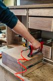 Red pneumatic stapler in a furniture workshop. Master nails a dong on the drawers royalty free stock photos