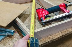 Red pneumatic stapler nails the bottom to the drawer. Stapler gun protective gloves on wood board construction concept stock photos