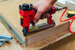 Red pneumatic stapler nails the bottom to the drawer. Stapler gun protective gloves on wood board construction concept stock image