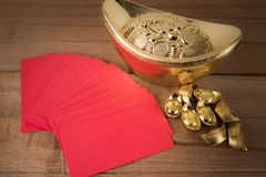 Red pocket and ancient Chinese golden ingots on wooden Royalty Free Stock Image