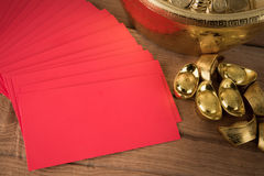 Red pocket and ancient Chinese golden ingots on wooden Stock Photography