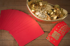 Red pocket and ancient Chinese golden ingots on wooden Stock Image