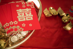 Red pocket and ancient Chinese golden ingots on wooden stock photo