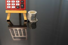 Red pocket calculator beside a stack of coins stock photos