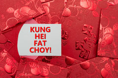 Red pockets with a card of KUNG HEI FAT CHOY. Red pockets with a card written KUNG HEI FAT CHOY Royalty Free Stock Photos