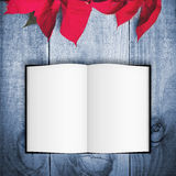Red poinsettia Christmas flower on wooden background. Open book Stock Photos