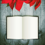 Red poinsettia Christmas flower on wooden background. Open book Stock Images