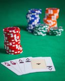 Red poker chips stacked on green table Stock Photos