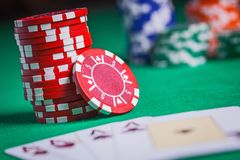 Red poker chips stacked on green table Stock Images