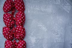 Red polka dot bows. Plush bow A toy. Light background under the concrete. Space for text royalty free stock photos
