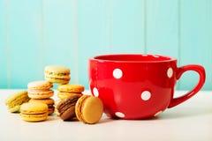 Red polka dot coffee mug with macarons Royalty Free Stock Photos