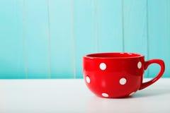 Red polka dot coffee mug. On pastel blue background Royalty Free Stock Image