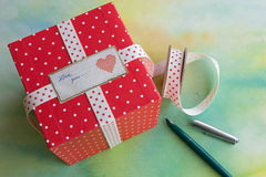 Red polka dot gift box. Closeup of red polka dot gift box with ribbon and label with the message Love you Stock Images