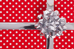 Red polka dot gift with silver bow and ribbon Royalty Free Stock Photos