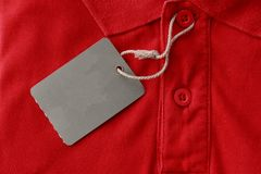 Red polo shirt. Close up red polo shirt with blank tags for sell at the shop Stock Photos