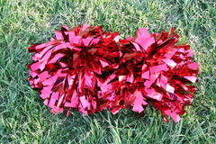 Red Pom Poms. Two red pom Poms set out on the grass Royalty Free Stock Photos