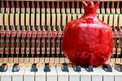 Red pomegranate bibelot on the close up image of grand piano keys and interior background. Red pomegranate bibelot on the close up image of grand piano keys and Royalty Free Stock Photo