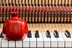 Red pomegranate on the close up image of grand piano keys and interior showing strings, hammer and structure background stock photos