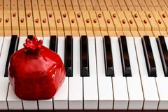 Red pomegranate on the piano keys royalty free stock image