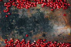 Red pomegranate seeds borders. Over black rustic background Royalty Free Stock Image