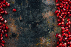 Red pomegranate seeds borders. Over black rustic background Stock Image
