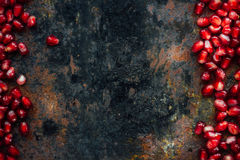 Red pomegranate seeds borders. Over black rustic background Royalty Free Stock Photo
