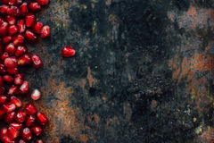 Red pomegranate seeds borders. Over black rustic background Stock Photo