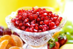 Red pomegranate seeds in a bowl with fresh fruits stock images