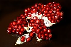 Red pomegranate seeds on a brown  background. Red pomegranate seeds scattered on a brown plate. The flesh is translucent allows you to see inside the seed Stock Photos