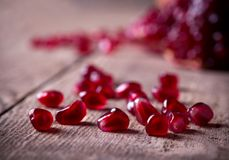 Red pomegranate seeds on old wooden table Stock Photography