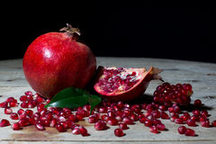 Red Pomegranate with Slices and Seeds on an Old Wooden Planks On Black Royalty Free Stock Image