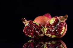 Red pomegranates lie in front of a dark background and are reflected on the ground