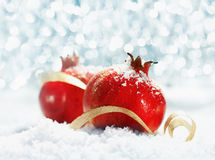 Red pomegranates with party lights. Red pomegranates decorated with a curled gold ribbon and dusted with snow against a sparkling bokeh of Christmas party lights royalty free stock photos