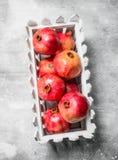 Red pomegranates in a plastic box stock photo