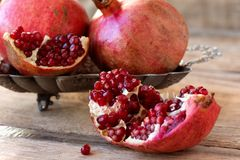 Red pomegranates on a plate on old wooden table. Red juicy pomegranate on plate lying on wooden table from old boards Stock Images