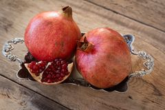 Red pomegranates on a plate on old wooden table. Red juicy pomegranate on silver plate lying on wooden table from old boards Royalty Free Stock Photography