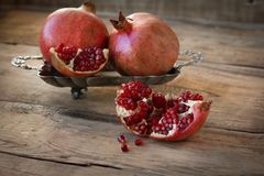 Red pomegranates on a plate on old wooden table. Three red juicy pomegranate on plate lying on wooden table from old boards Stock Image