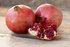 Red pomegranates on a plate on old wooden table. Two red juicy pomegranate on wooden table from old boards Royalty Free Stock Photography