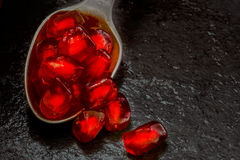 Red pomegranates seeds in a silver spoon Stock Photos
