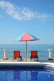 Red pool chairs ocean sky Royalty Free Stock Images