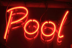 Red pool neon sign. At night outside a snooker club Stock Photos