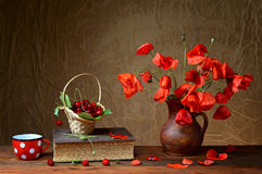Red poppies in a ceramic vase, books,cherries and metal pots on the table Stock Image